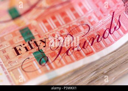 Sullo sfondo di un gran mucchio di usato cinquanta UK pound banconote sterling