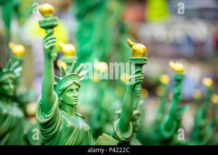Riga con generic Statua della Libertà statue (messa a fuoco selettiva) venduti come souvenir in un negozio di NYC. Foto Stock