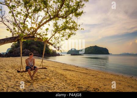 Ragazzo giovane gode di tramonto n Ko Hong Island in Thailandia