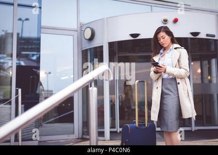 Imprenditrice utilizzando il telefono cellulare al di fuori di un hotel Foto Stock