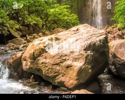 Primo piano di rocce ai piedi del Carbet Falls, uno dei tre cascate nella foresta pluviale tropicale sul fiume Carbet, Guadalupa isola dei Caraibi francesi. Le cascate sono uno dei più popolari siti di visitatori.
