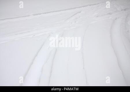 Tracce dalle ruote della vettura su una coperta di neve su strada. Pericoloso e scivolosa la sterzata del veicolo . Foto Stock