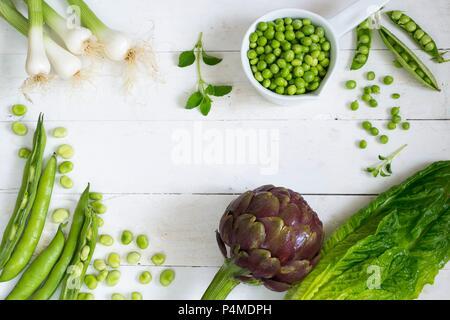 Una disposizione di verdure con una grande carciofo e piselli Foto Stock