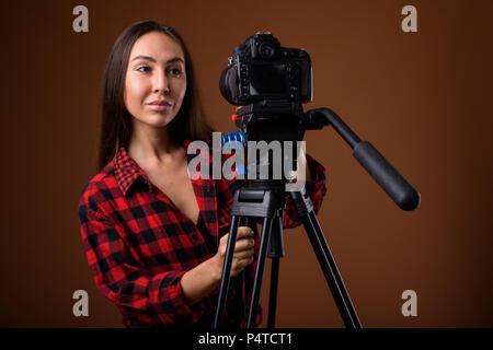 Studio shot del giovane bella donna vlogging contro dorso bruno Foto Stock