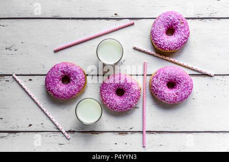 Quattro ciambelle rosa, due bicchieri di latte e le cannucce in legno bianco Foto Stock