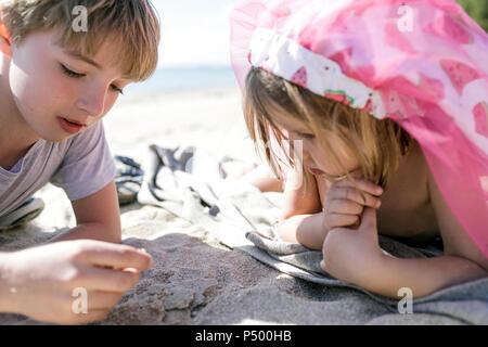 Un ragazzo e la sua sorellina sdraiato sulla spiaggia Foto Stock