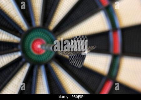 Un dardo colpisce il bersaglio in centro di dartboard Foto Stock