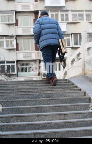 Persona anziana a salire le scale Foto Stock
