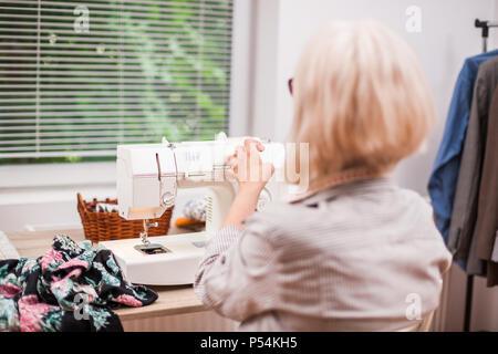 Donna adulta è cucito nel suo studio. Foto Stock