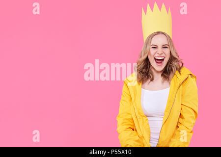 Bella ragazza adolescente di colore giallo luminoso giacca e cappellino gridando con entusiasmo. Raffreddare attraente giovane donna moda ritratto su rosa pastello. Foto Stock