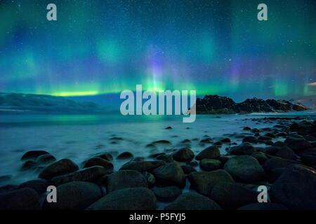 Incredibile Aurora Boreale ballare sulla famosa spiaggia di Uttakleiv durante una fredda notte artica sulle Isole Lofoten arcipelago in inverno, Norvegia e Scandinavia Foto Stock