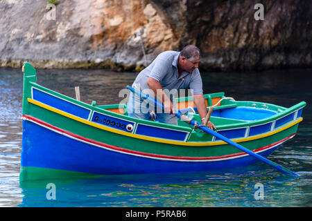 Un pescatore di righe il suo tradizionale maltese barca a remi nella baia di Xlendi a raccogliere le gabbie di aragosta. Foto Stock