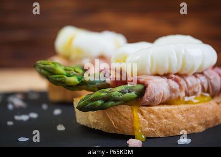Toast alla griglia con asparagi con pancetta e uova in camicia su sfondo di legno Foto Stock