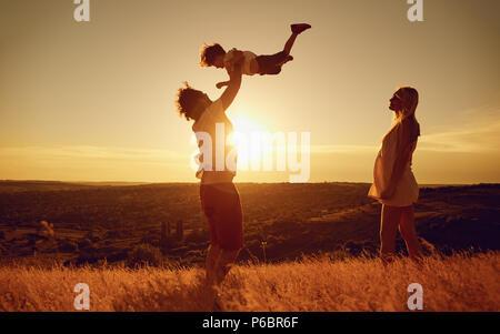 La famiglia felice divertirsi giocando al tramonto sulla natura.