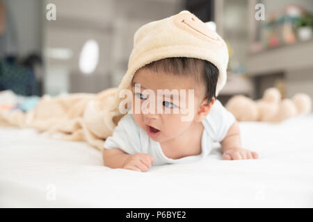 Ritratto di un bambino gattona sul letto in camera sua, adorabile baby boy in bianco e luminosa camera da letto, neonato relax nel letto, vivaio di giovani bambini Foto Stock
