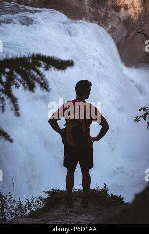 Uomo in piedi con le mani sui hip vicino a cascata Foto Stock