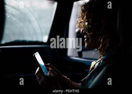 Bella bella età media donna viaggiare all'interno di una vettura shile pioggia fuori. utilizzando uno smartphone che consente di connettersi e di chiamare i tuoi amici e incontrare per la notte a celeb Foto Stock