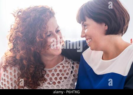 Coppia di amici di sesso femminile sorridente insieme ogni altra. Godetevi friendshiop e relazione. caucasian belle giovani donne con sfondo bianco