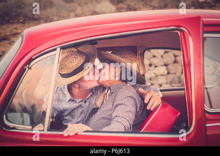 Coppia di anziani con cappello, con occhiali, con il grigio e il bianco dei capelli, con camicia casual, su vintage auto rossa in vacanza godendosi il tempo e la vita. Con un chee