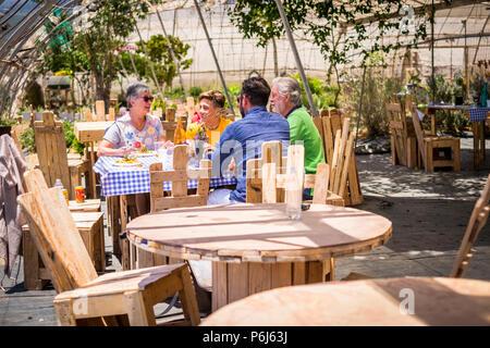 La famiglia a pranzo insieme naturale outdoor luogo scenico con un sacco di legno riciclato mobili realizzati con le palette. Godetevi il sorriso e attività di svago di cauca