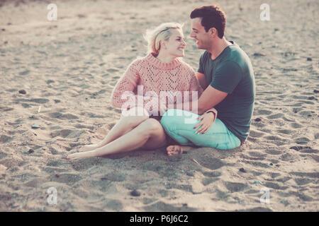 Bellissimo modello giovane caucasico giovane donna e uomo rimanere nell'amore abbracciando e seduto sulla spiaggia. bionda e capelli neri in rapporto all'aperto leisu Foto Stock