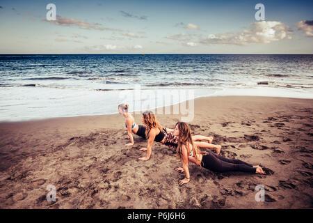 Tre cacuasian giovani donne facendo pilates sulla riva vicino alle onde e l'oceano. outdoor le attività per il tempo libero sport e stile di vita per il fitness beauti