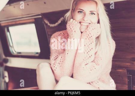 Bella bionda modello caucasico bianco pelle con bellezza viso il sorriso a voi guardando la telecamera. Sedetevi in un furgone con interni in legno di pronto a viaggiare Foto Stock
