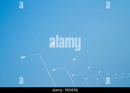 Via la luce pali contro il cielo blu Foto Stock