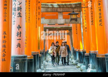 I turisti giapponesi esplorare Fushimi Inari Taisha a Kyoto, in Giappone. Lungo il percorso principale ci sono più di 10000 torii gates. Foto Stock