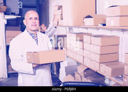 Femmina e positivo maschio adulto carrello di trasporto delle scatole di cartone in deposito Foto Stock