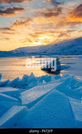 Jokulsarlon laguna glaciale, Islanda, l'Europa. Blocchi di ghiaccio in laguna gelata su un tramonto in inverno. Foto Stock