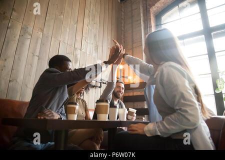 Felice diversi amici dando alta cinque di refrigerazione in cafe Foto Stock