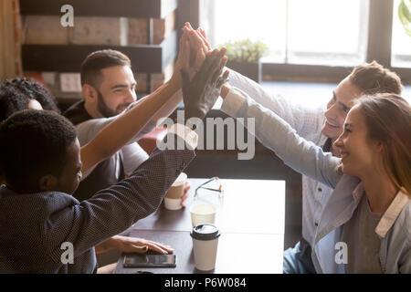 Multirazziale amici dando alta cinque seduti fuori in coffee shop Foto Stock