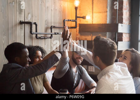 Sorridente millennial dando alta cinque durante la riunione in cafe Foto Stock