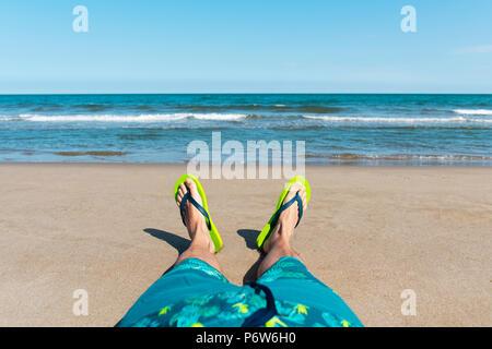 Primo piano delle gambe di un giovane uomo caucasico rilassante sulla spiaggia, che indossa un costume da bagno blu e una coppia di green flip-flop, con l'oceano in retro Foto Stock