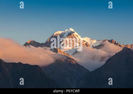 Nuova Zelanda, Isola del Sud, West Coast, villaggio Fox Glacier, Lago Matheson, riflessione di Mt. Tasman e Mt. Cuocere, crepuscolo Foto Stock