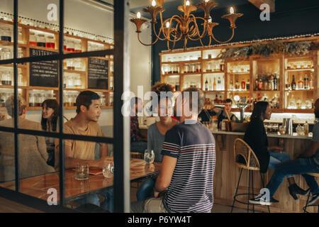 Diversi giovani amici seduti in un bar con bevande insieme