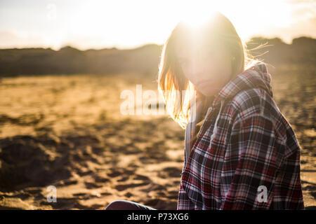 Grande bella luce dorata in un tramonto con la bionda attraente persone molde seduto alla spiaggia. vacanze e viaggi wanderlust per active girl look Foto Stock