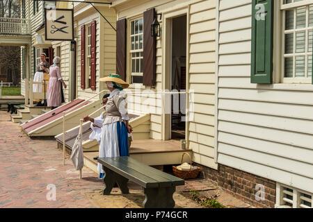Williamsburg, Virginia, Stati Uniti d'America - 1 Aprile 2018 : donna vestito in abiti storici in piedi di fronte a una casa