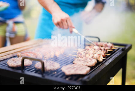 Felice gli studenti aventi un barbecue sul giorno di estate Foto Stock