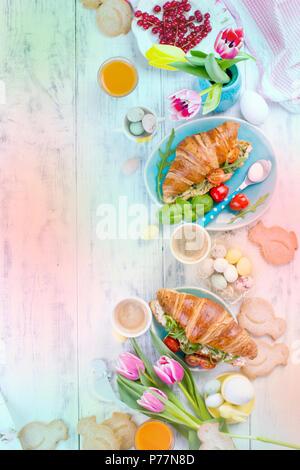 Colazione di pasqua. Un family colazione con croissant con insalata di rucola e formaggio e caffè aromatici. Tulipani freschi di colore rosa e uova di differenti colori e decorazioni di Pasqua. Spazio libero per il testo Foto Stock