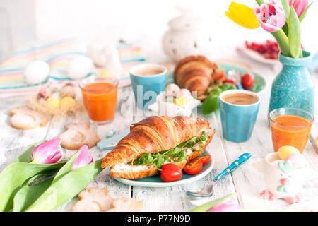 Sfondo con colori diversi. Un family colazione con croissant con rucola e formaggi e caffè aromatico, uova di differenti colori, luminoso piatti e decorazioni di Pasqua, conigli in ceramica Foto Stock