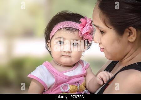 Triste Indiano/bambino asiatico ragazza madre in braccio. Foto Stock
