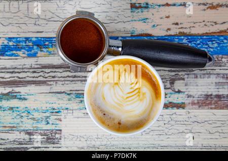 Una tazza di latte, cappuccino o caffè espresso con latte mettere su un tavolo in legno scuro con chicchi di caffè tostati Foto Stock