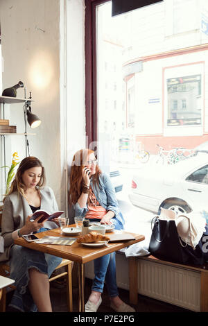 Le donne la lettura e chattare su telefono cellulare in cafe Foto Stock
