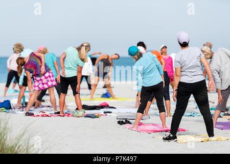 Venezia, Stati Uniti d'America - 29 Aprile 2018: Piccola pensione florida città, paese o di una comunità di villaggio con persone che praticano esercizio di yoga sulla spiaggia, stretchin Foto Stock