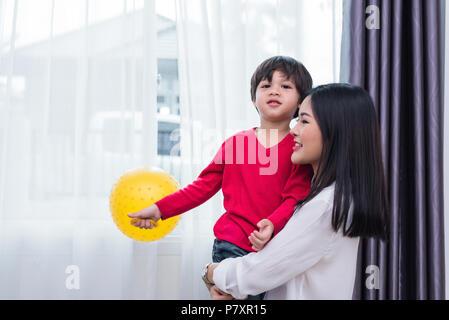 Mom abbraccio e portare il suo figlio. Preparazione per inviare i suoi figli si torna a scuola in mattina. Istruzione e il ritorno a scuola concetto. La famiglia felice e amorevole di Foto Stock