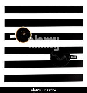 Tazze da caffè su le strisce bianche e nere Foto Stock