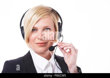 Bella sorridente operatore di call center, donna bionda vestita in giacca nera prima di sfondo bianco con copyspace Foto Stock