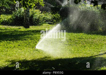 Innaffiamento Automatico Degli Impianti Sprinkler Nel Giardino In Una Calda  E Soleggiata Giornata Estiva Per Aggiornare